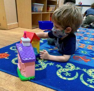 masked boy playing in kids zone